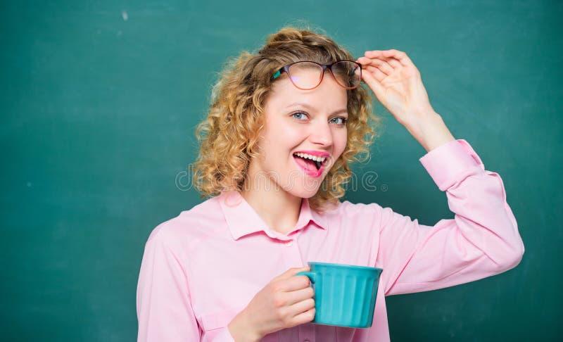 Dosis de cafeína El profesor bebe café con fondo de tiza Las mujeres disfrutan del café Carga energética para todo el día Inspira imagen de archivo
