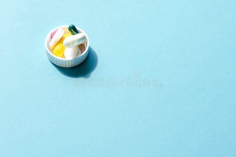 Dosis der farbigen Pillen in der Kappe des Pakets der Pillen stockbilder
