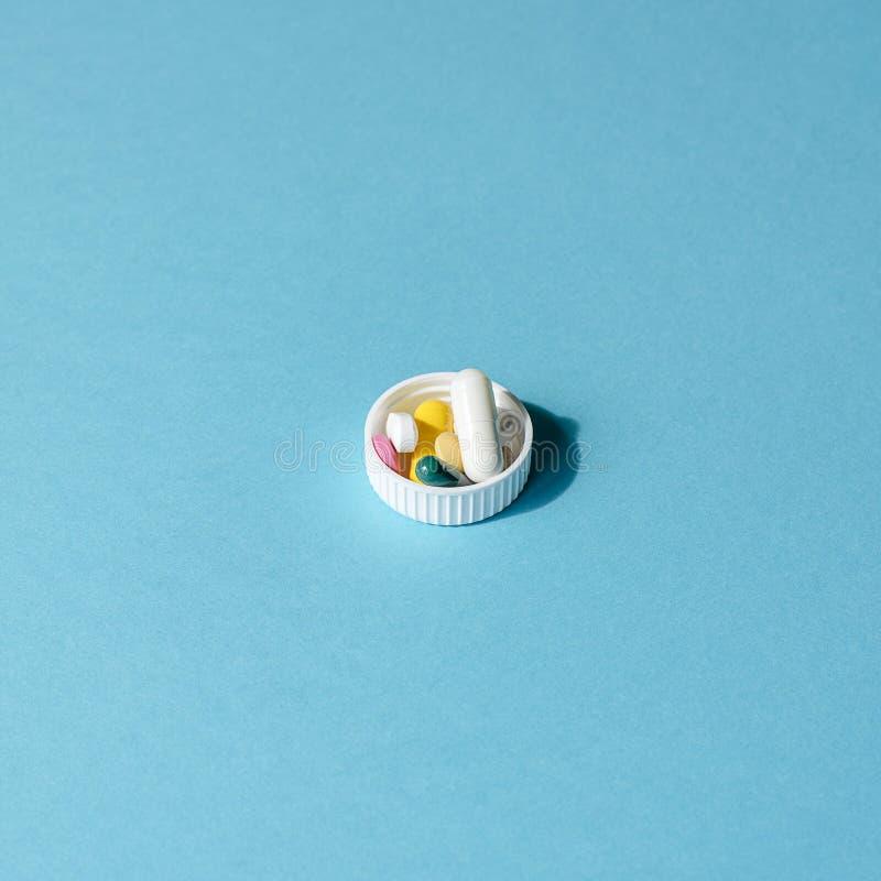 Dosis der farbigen Pillen in der Kappe des Pakets der Pillen stockfotos