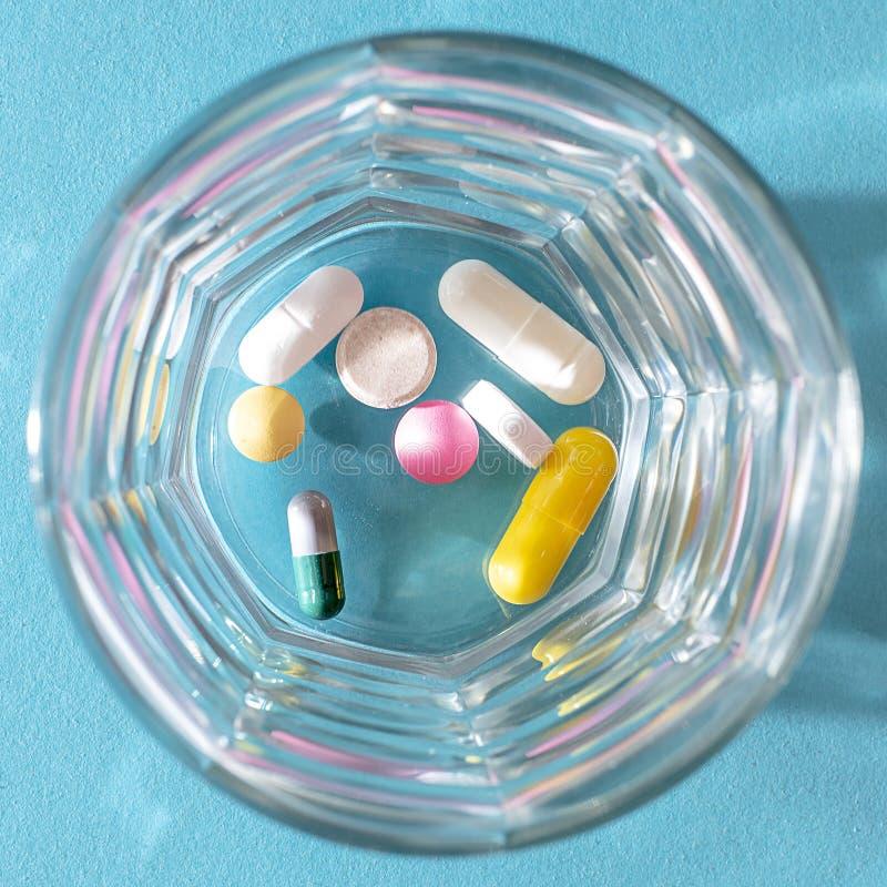 Dosis von bunten Pillen in einer transparenten Glasschale auf einem blauen Hintergrund lizenzfreie stockfotografie