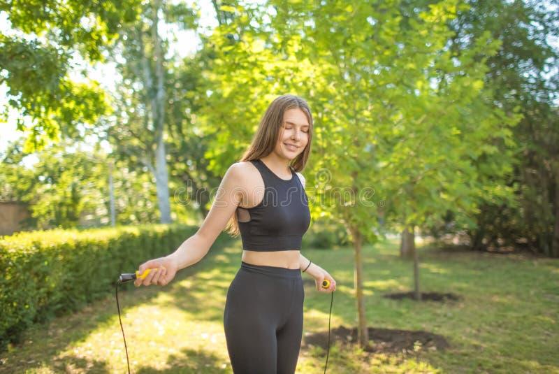 Doskonale i rozochocona dama w czarnym wierzchołku czarnych leggings i trzyma arkanę w ona ręki i doskakiwanie Sporta pojęcie zdjęcie royalty free