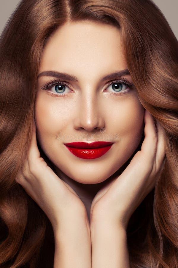 Doskonalić żeński twarzy zbliżenia portret Ładna kobieta z kędzierzawym błyszczącym włosianym i czerwonym wargi makeup zdjęcie stock