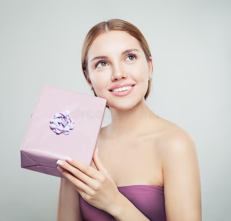 Doskonalić młoda kobieta z prezentem i ślicznym uśmiechem zdjęcie stock