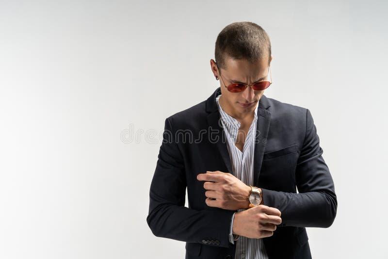 Doskonalić ostatni szczegół Przystojny młody biznesmen przystosowywa jego rękawy podczas gdy stojący przeciw popielatemu tłu obrazy royalty free