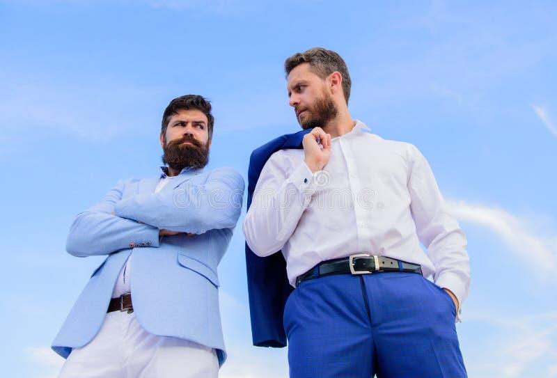 Doskonalić w każdy szczególe Biznesowi mężczyzna stoją z powrotem popierać niebieskiego nieba tło Brodaci przedsiębiorcy pozuje p zdjęcie royalty free