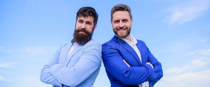 Doskonalić w każdy szczególe Ludzie biznesu pojęć Brodaci ludzie biznesu pozuje pewnie Biznesowych mężczyzn stojaka błękit fotografia stock