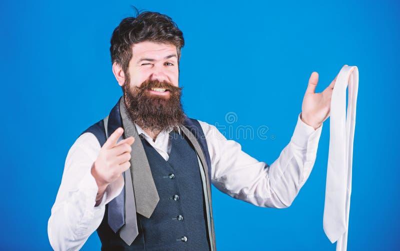 Doskonali? akcesorium dla garnituru Elegancki biznesowy m??czyzna wskazuje klasycznego krawat i trzyma Modnisia wybiera? zdjęcie royalty free