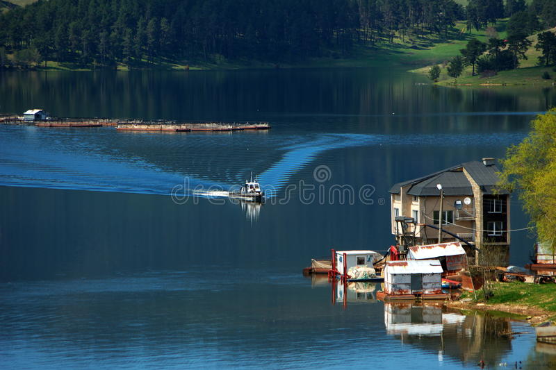 Dospat dam. Fish farming village called Dospat, captured in Bulgaria. Little fishing boat, floating trough the dam. Behind the boat there are cages for fish stock images