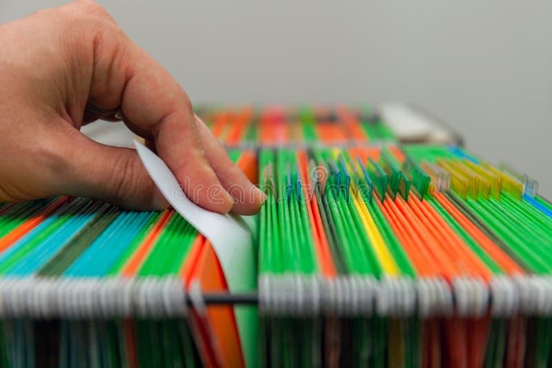 Dossiers accrochants colorés de fond abstrait dans le tiroir Équipe la main image libre de droits