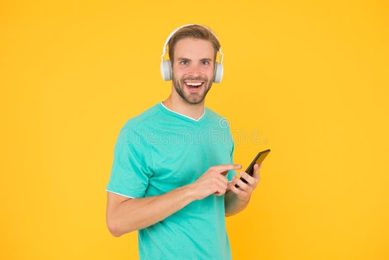 Dostaje muzyczn? rodzinn? prenumerat? Mężczyzna słucha muzycznych nowożytnych hełmofony i smartphone S?ucha dla bezp?atnego Ciesz obrazy stock