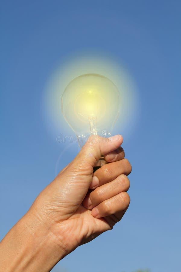Dostaje pomysł, ludzka ręka z lekką lampą. zdjęcia royalty free