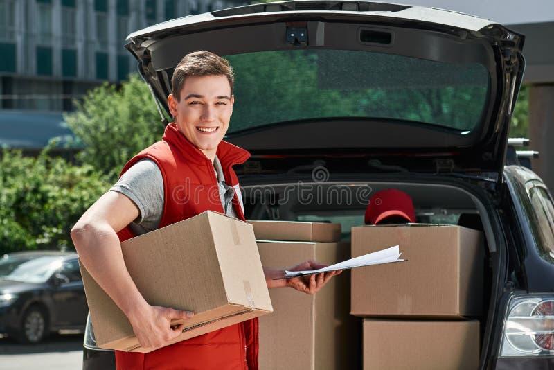 Dostarczać znakomitej obsługi klientej Listonosz dostaje pakuneczki od samochodu fotografia royalty free