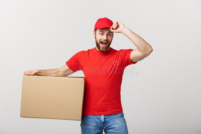Dostarcza pojęcie: Młody caucasian przystojny doręczeniowy mężczyzna trzyma pudełko na ramieniu Nad popielatym tłem zdjęcie royalty free