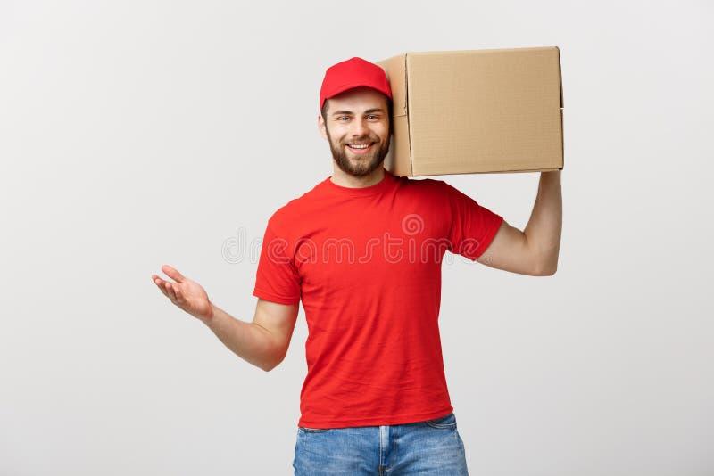 Dostarcza pojęcie: Młody caucasian przystojny doręczeniowy mężczyzna trzyma pudełko na ramieniu Odizolowywający nad popielatym tł zdjęcie royalty free