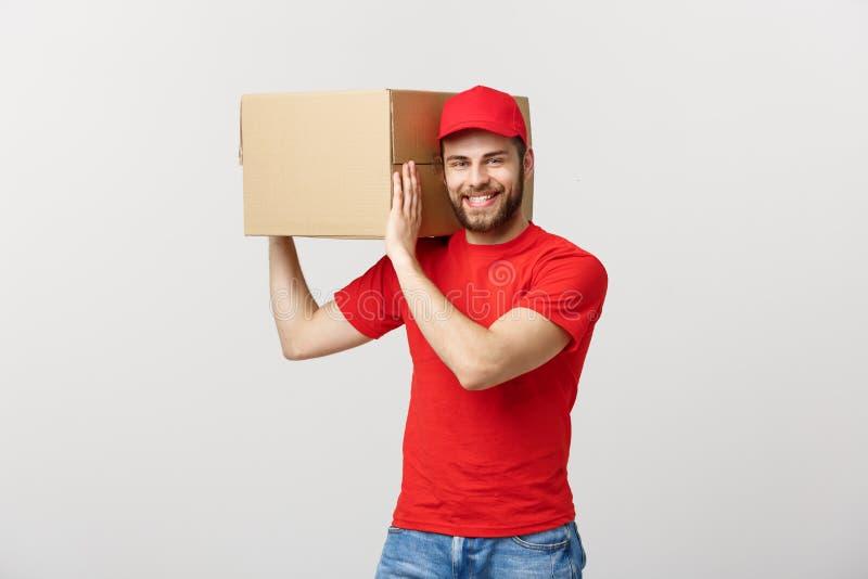 Dostarcza pojęcie: Młody caucasian przystojny doręczeniowy mężczyzna trzyma pudełko na ramieniu Odizolowywający nad popielatym tł zdjęcie stock