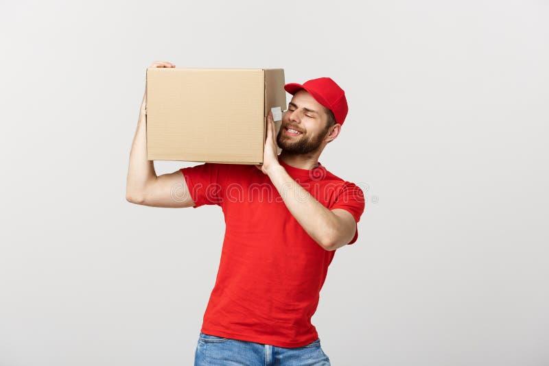 Dostarcza pojęcie: Młody caucasian przystojny doręczeniowy mężczyzna trzyma pudełko na ramieniu Odizolowywający nad popielatym tł obrazy royalty free