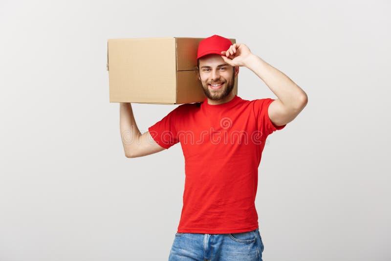 Dostarcza pojęcie: Młody caucasian przystojny doręczeniowy mężczyzna trzyma pudełko na ramieniu Odizolowywający nad popielatym tł fotografia royalty free
