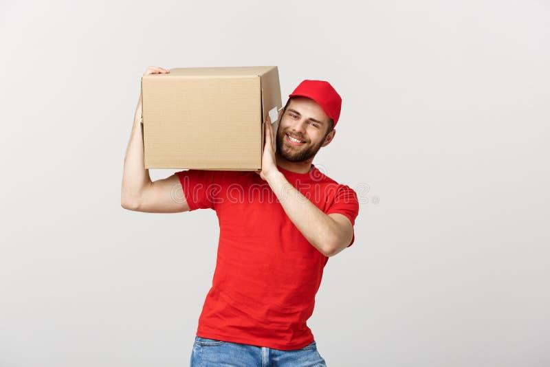 Dostarcza pojęcie: Młody caucasian przystojny doręczeniowy mężczyzna trzyma pudełko na ramieniu Odizolowywający nad popielatym tł zdjęcia stock
