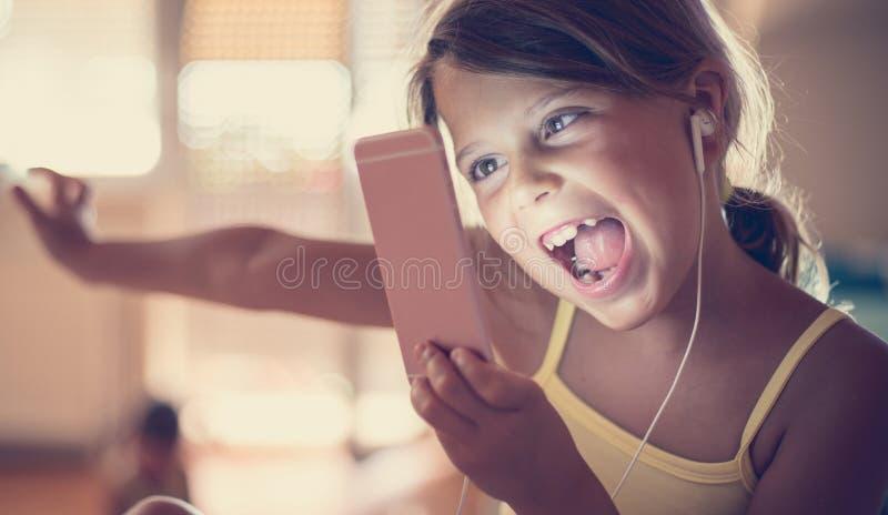 She dostawać wszystkie jej faworyta nastraja na jej telefonie komórkowym fotografia stock