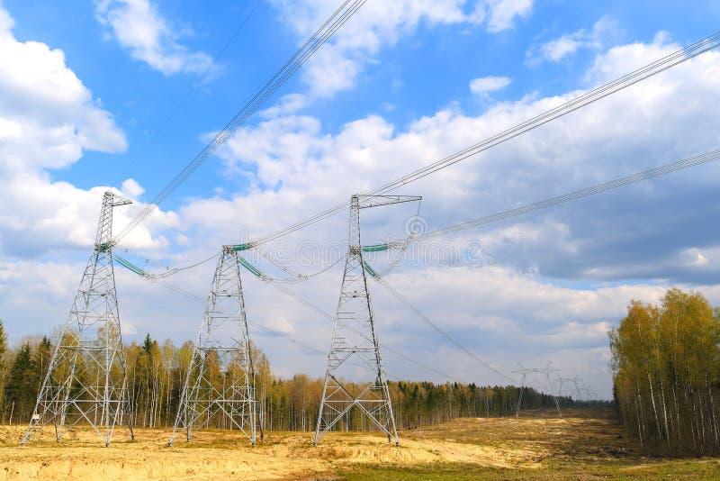 Dostawa elektryczność pod kontraktem sąsiedni stany Wysokonapi?ciowe linie energetyczne i niebieskie niebo z chmurami fotografia stock