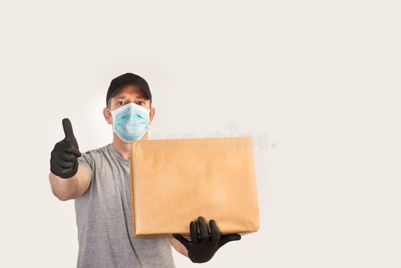 Dostawca z rękawiczkami medycznymi i maską trzymający pudełko i z kciukiem w górę zdjęcie royalty free