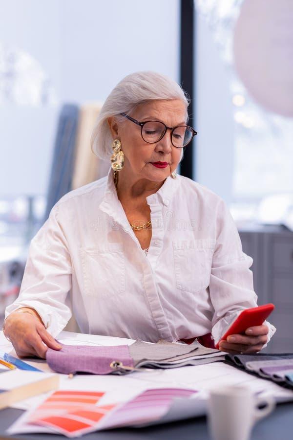Dostojny biznesowy madam sprawdza wymianę na telefonie w rok fotografia stock