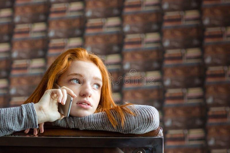 Dosyć śliczna dziewczyna opowiada na telefonie komórkowym z czerwonym włosy zdjęcie royalty free
