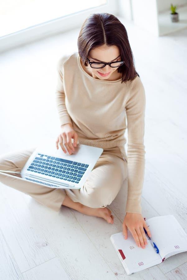 Dosyć śliczna dziewczyna w szkłach siedzi na podłoga, trzyma laptop zdjęcia stock