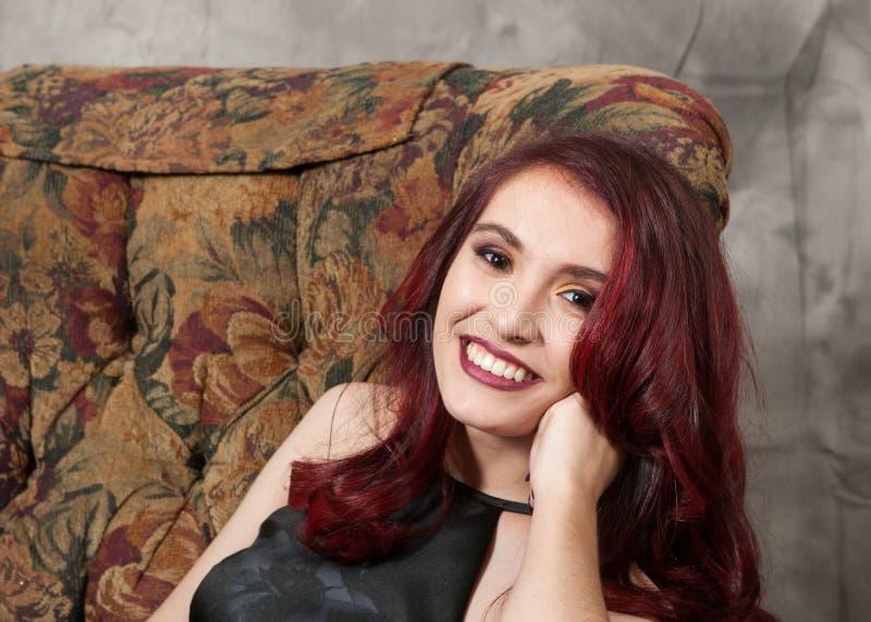Dosyć brązowooka rudzielec dziewczyna opiera w krześle fotografia stock