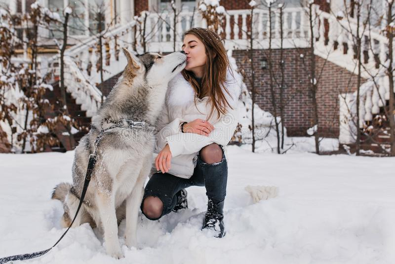 Dosyć caucasian dama całuje jej łuskowatego psa podczas spaceru w zima dniu w białej kurtce Atrakcyjna młoda kobieta jest ubranym obraz stock