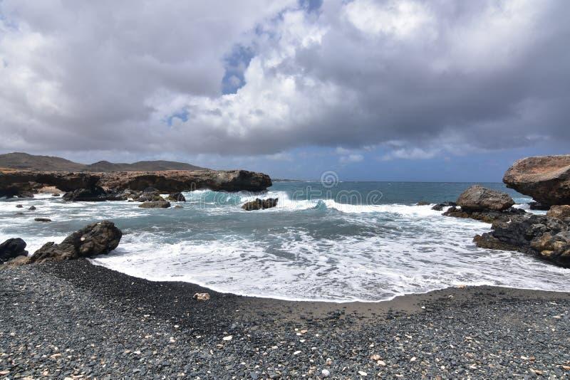 Dosyć Czarna piasek plaża na Aruba ` s wschodu linii brzegowej zdjęcie stock