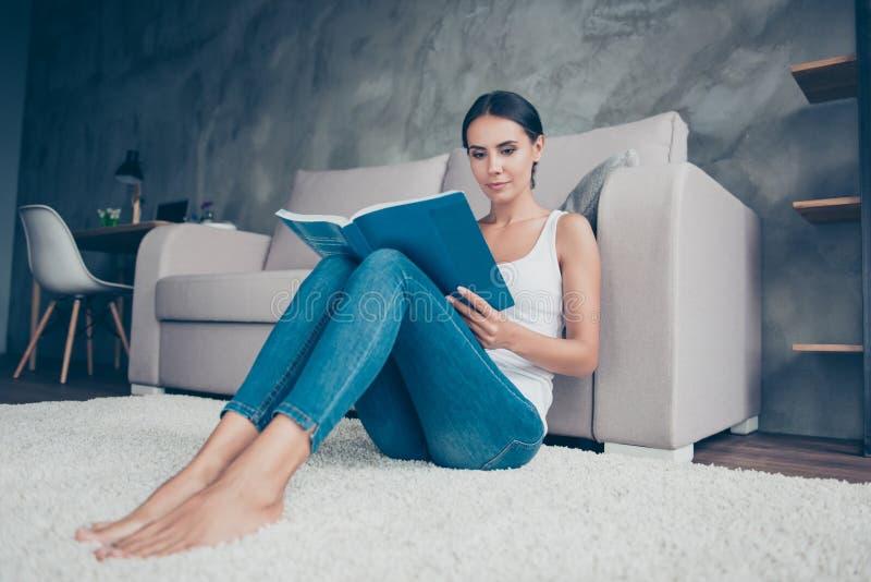 Dosyć, czarujący, mądra kobieta siedzi blisko kanapy na podłoga, h zdjęcia royalty free