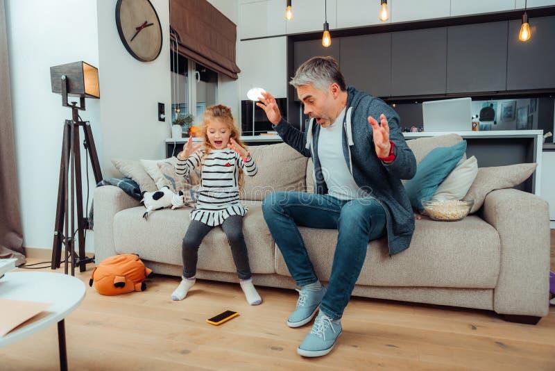 Dosyć długowłosa dziewczyna w sukni i jej siwowłosym ojcu patrzeje straszący zdjęcia stock