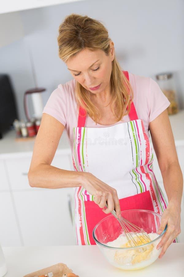 Dosyć dojrzała kobieta miesza składniki gotować smakowitego deser fotografia royalty free