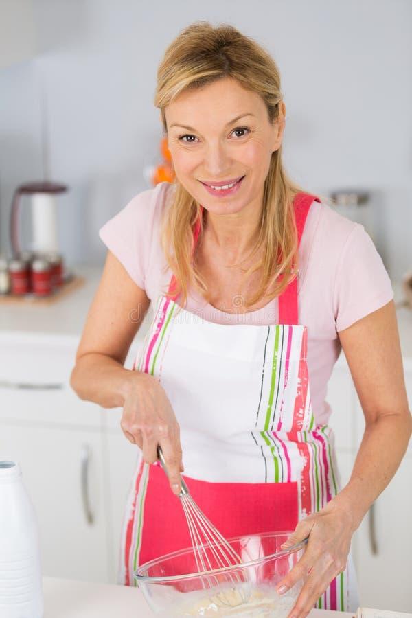 Dosyć dojrzała kobieta miesza składniki gotować smakowitego deser fotografia stock