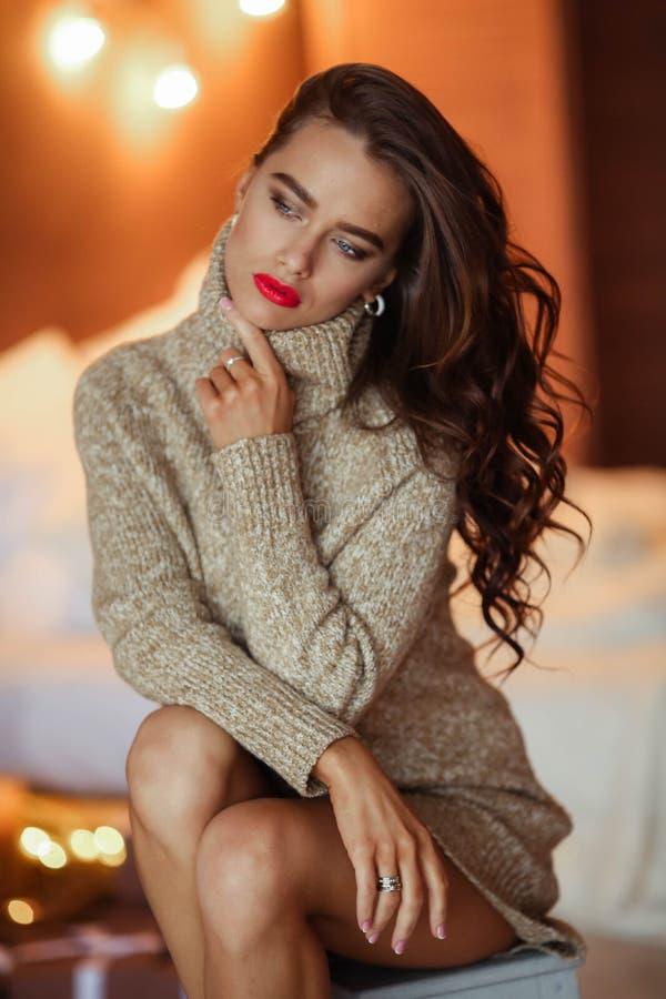 Dosyć elegancka dziewczyna w sukni z fryzury i makeup obsiadaniem przy kanapą Moda splendoru portret zdjęcie royalty free
