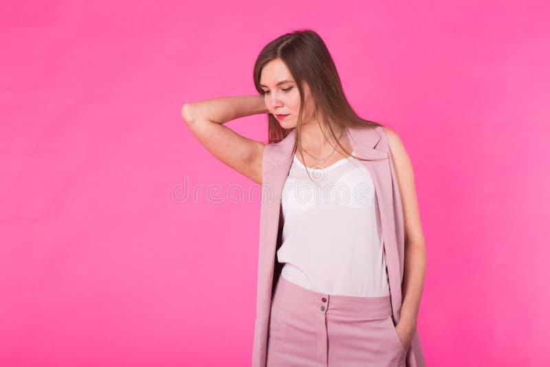 Dosyć elegancka dziewczyna z długie włosy pozować przeciw różowemu tłu Moda portret młoda szczęśliwa uśmiechnięta kobieta zdjęcie royalty free