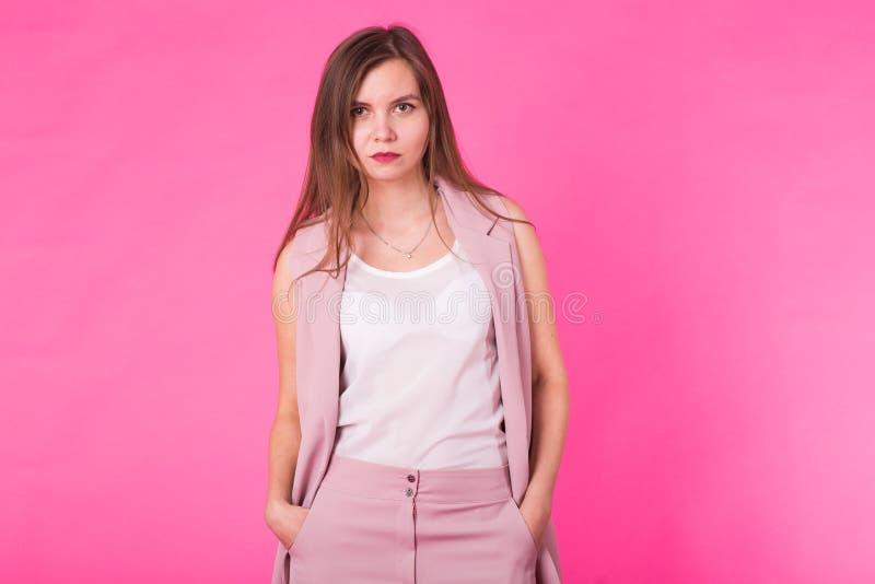 Dosyć elegancka dziewczyna z długie włosy pozować przeciw różowemu tłu Moda portret młoda szczęśliwa uśmiechnięta kobieta obrazy stock