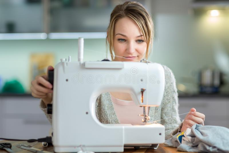 Dosyć, młodej kobiety szyć odziewa z szwalną maszyną obrazy stock