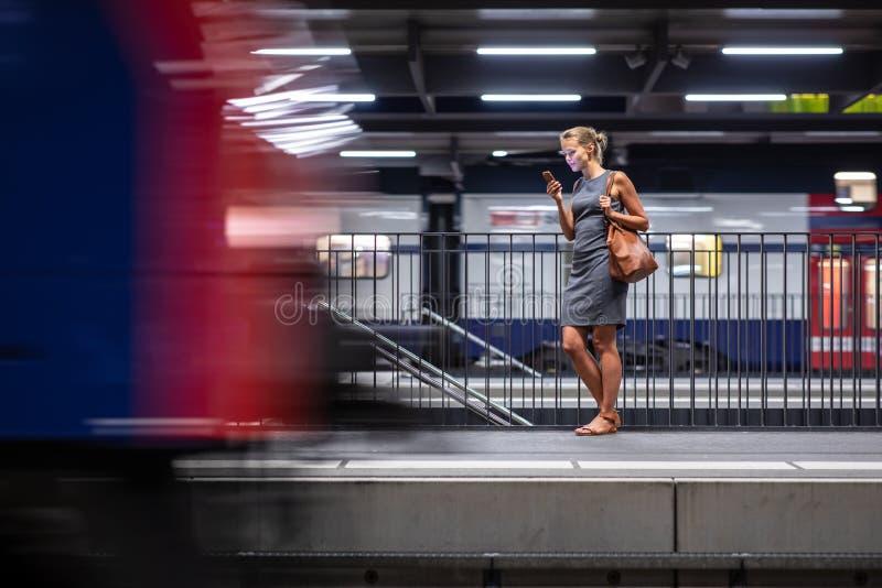 Dosyć, młody żeński dojeżdżający czekać na jej dziennego pociąg zdjęcie royalty free