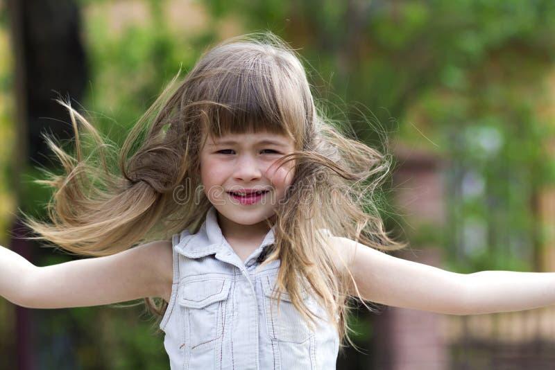 Dosyć mała preschool dziewczyna w sleeveless biel sukni z pięknym długim blondynem dmuchającym wiatrem, śmiesznym bezzębnym uśmie zdjęcia royalty free