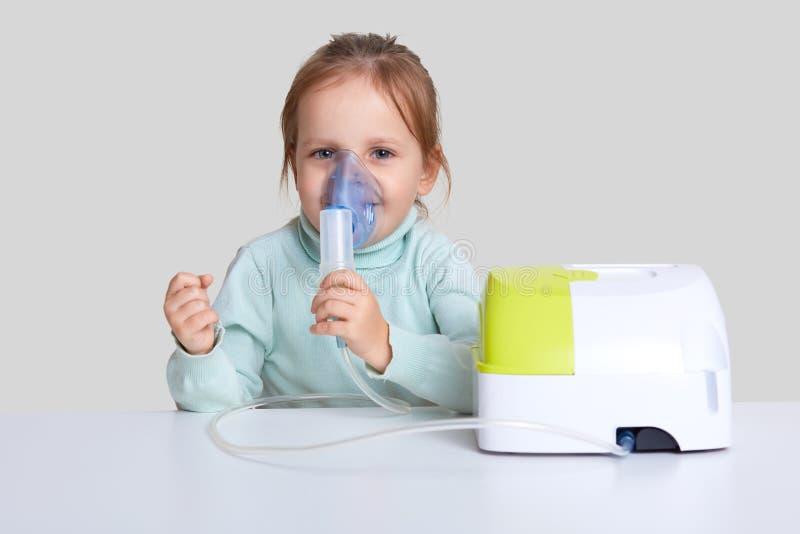 Dosyć mały dziecko używa nebulizer maskę dla inahlation, dba zdrowie, siedzi przy białym desktop, ubierającym w przypadkowej bluz fotografia royalty free