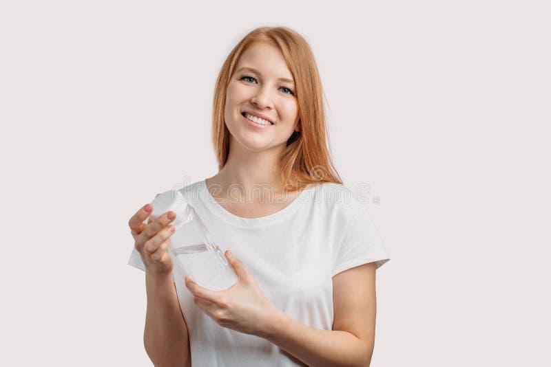 Dosyć miedzianowłosa kobieta zaczyna dzień z wodą fotografia stock