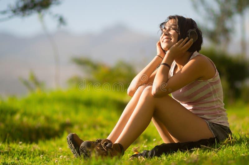 Dosyć nastoletni latynoski dziewczyny obsiadanie na trawie zdjęcie stock