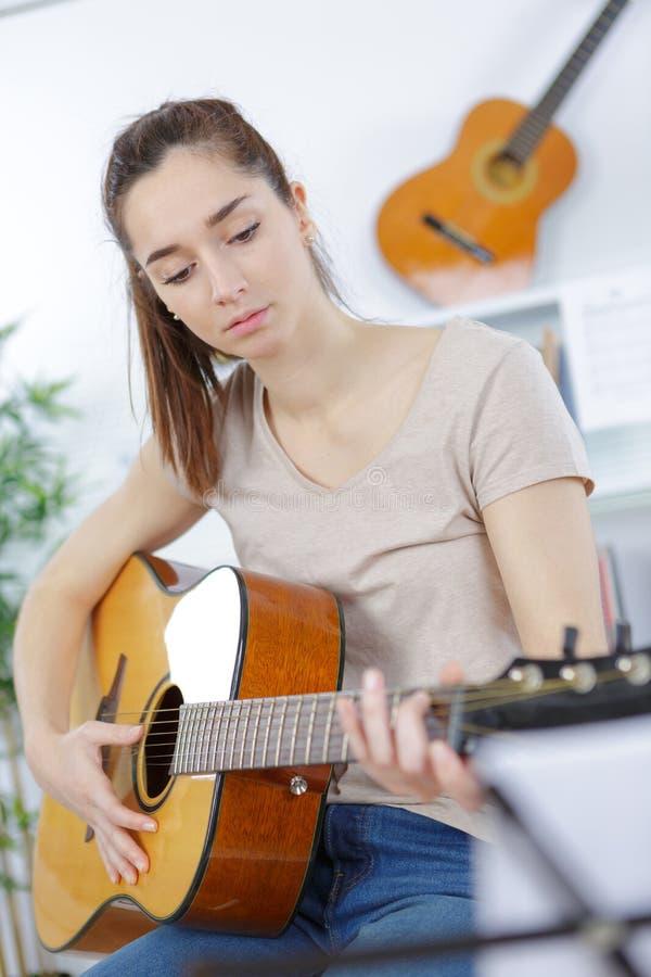 Dosyć nastoletnia dziewczyna bawić się gitarę fotografia royalty free