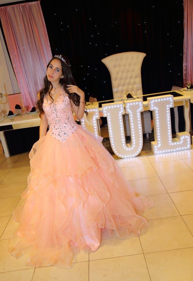 Dosyć nastoletniego quinceanera dziewczyny urodzinowa odświętność w princess sukni menchii przyjęciu, specjalny świętowanie dziew obrazy stock