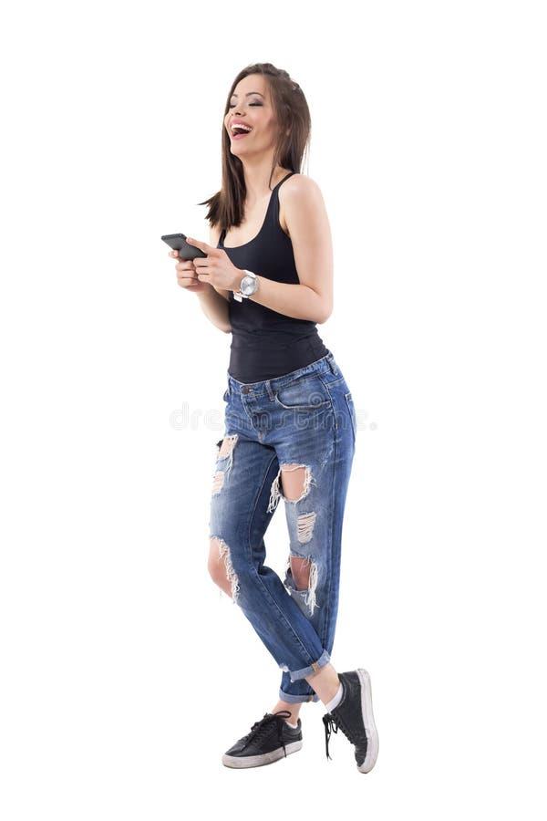 Dosyć nowożytna młoda kobieta śmia się serdecznie białego mienie telefon komórkowego w modnych drzejących cajgach obrazy royalty free