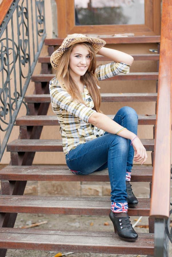 Dosyć ono uśmiecha się nastoletniej dziewczyny obsiadanie na schodkach obraz royalty free