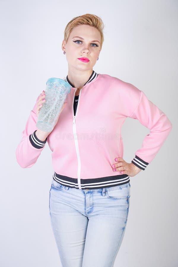 Dosyć plus wielkościowa krótkiego włosy kobieta z błękitną filiżanką woda blondynki dorosła dziewczyna jest ubranym sport różową  zdjęcie stock