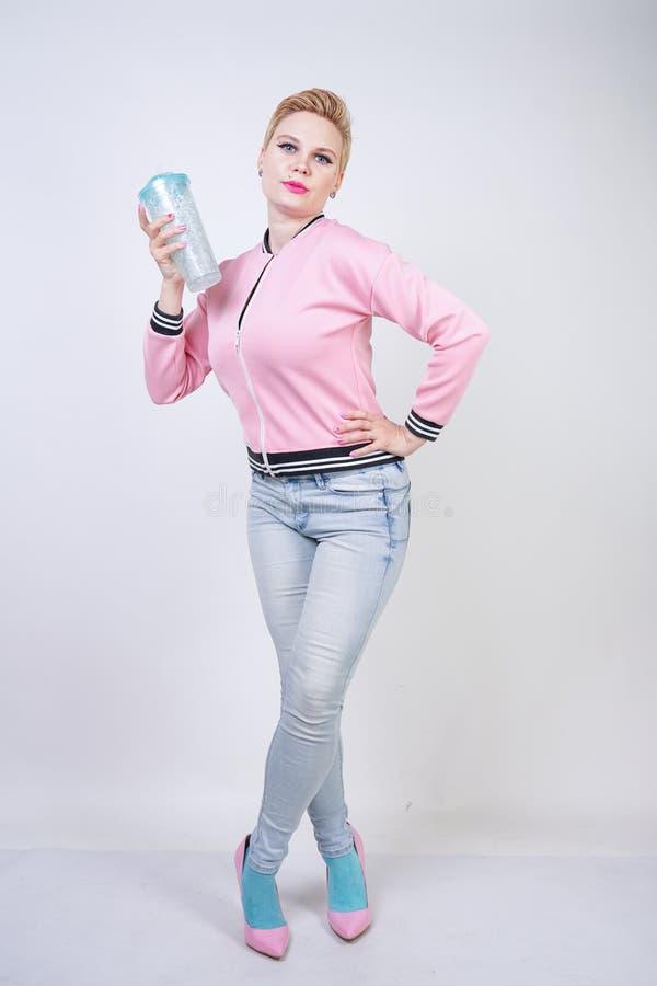 Dosyć plus wielkościowa krótkiego włosy kobieta z błękitną filiżanką woda blondynki dorosła dziewczyna jest ubranym sport różową  fotografia stock